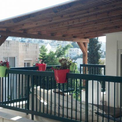 בניית פרגולה מעץ במרפסת בניין